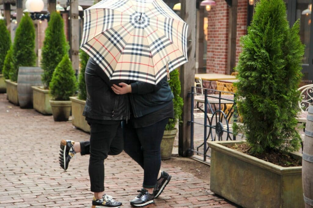 Mark and Pedro kissing under an umbrella